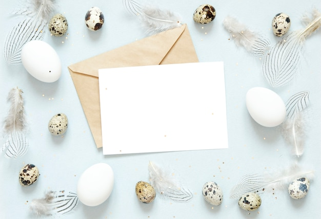 Blank greeting card, kraft envelope. easter composition with easter eggs and feathers on blue background.
