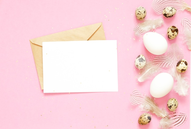 Blank greeting card, kraft envelope. easter composition with easter eggs and feathers on pink background.