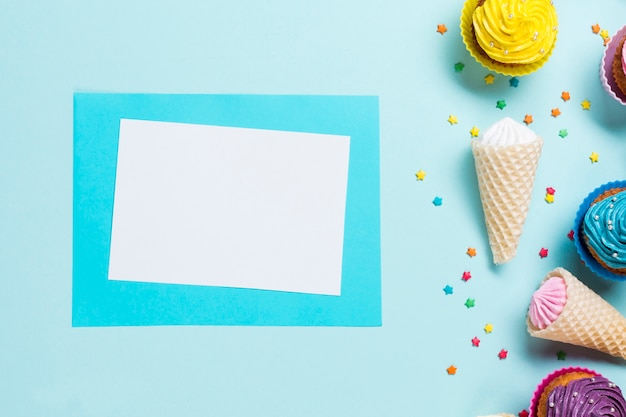 Blank greeting card near the sprinkles; waffle cones and muffins on blue backdrop