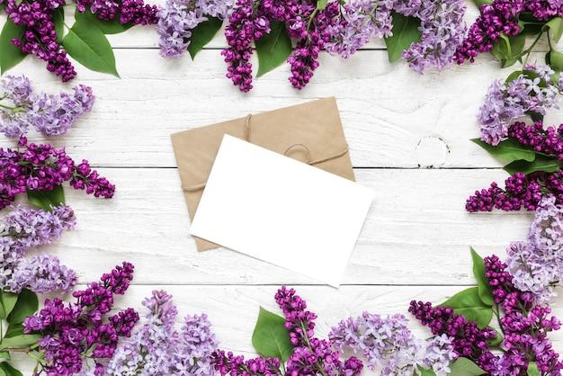 空白のグリーティングカードまたは白い木製のテーブルの上の紫色のライラックの花で作られたフレームでの結婚式の招待状