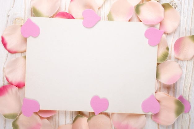 Blank greeting card on a pile of rose petals