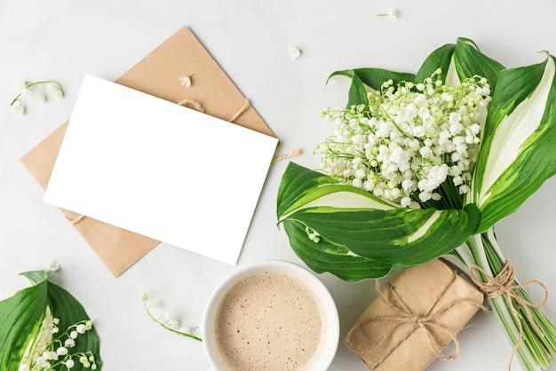 Пустая открытка, букет цветов весеннего ландыша, чашка кофе и подарочная коробка на белой поверхности