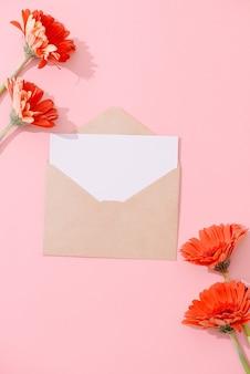Пустая открытка с коричневым конвертом и цветком герберы на розовом столе с винтажным тоном и виньеткой