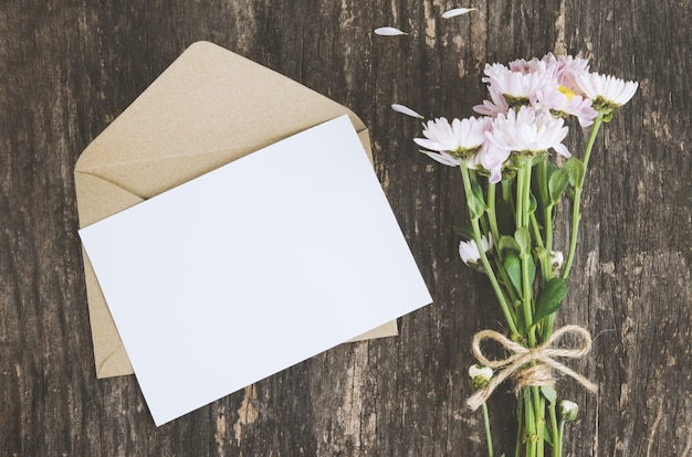 Blank greeting card with brown envelope and mum flowers on wooden table