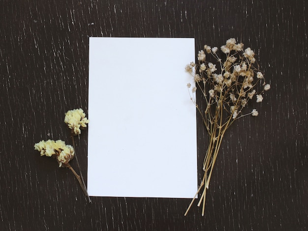 Blank greeting card with flower on rustic wood background for creative work design