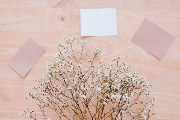 Blank greeting card with flower on rustic wood background for creative work.