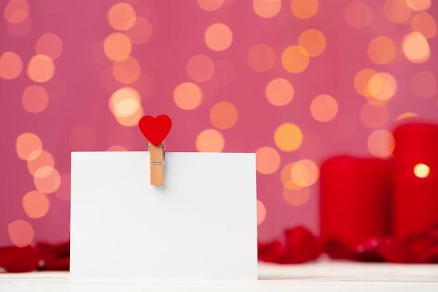 ピンクのボケ味の正面図に対してハートピン付きの空白のグリーティングカード