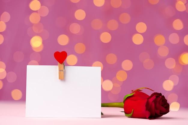 ピンクのボケ味に対するハートピン付きの空白のグリーティングカード