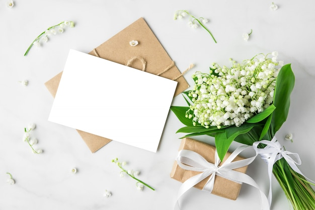 Blank greeting card with lily of the valley flowers bouquet and gift box on white.