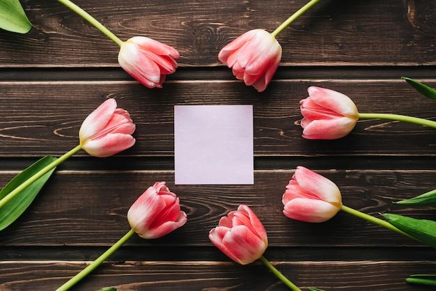Пустая открытка с розовыми тюльпанами и пустой стикер на деревянном столе