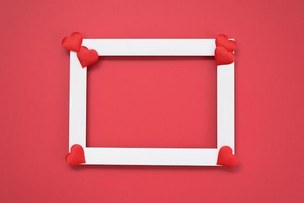 Пустая поздравительная открытка с местом для текста подарок дня валентинки с красной лентой и сердцами на красном фоне. макет.