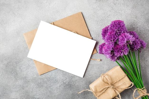 Пустая открытка с букетом фиолетовых полевых цветов и подарочной коробкой на бетонной поверхности