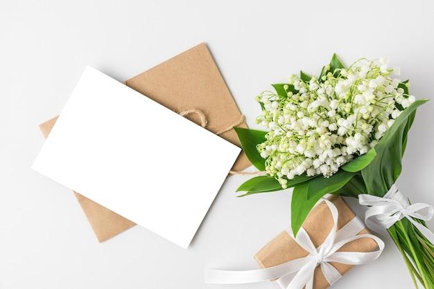 Пустая открытка с весенним букетом цветов ландыша и подарочной коробкой на белой поверхности