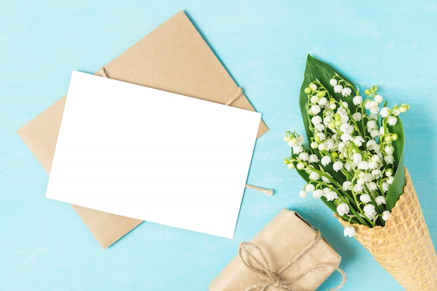 Blank greeting card with spring lily of the valley flowers in waffle cone with gift box on blue background. mock up. flat lay