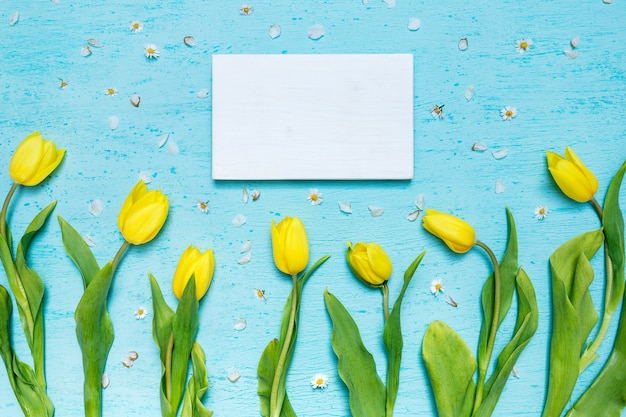 A blank greeting card and yellow tulips on a blue surface with tiny daisy flowers