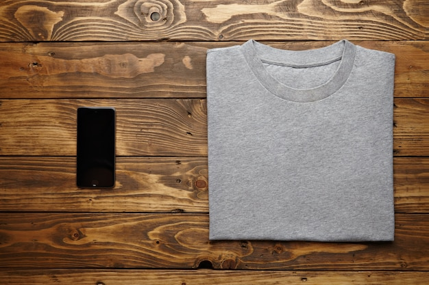 Blank grey t-shirt accurately folded near black smartphone gadget on rustic wooden table top view