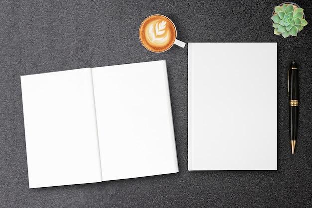 빈 하드 커버 캔버스 책 블랙 테이블에 디자인 책 표지를 모의
