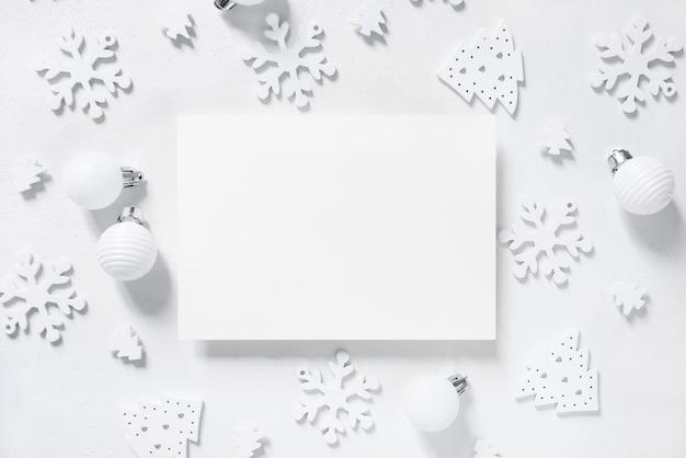 흰색 테이블에 흰색 크리스마스 장식이 있는 빈 가로 인사말 카드. 봉투 모형, 복사 공간이 있는 겨울 구성