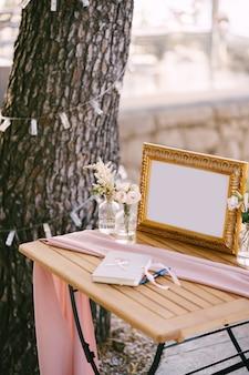 새겨진 프레임에 빈 핑크 목도리로 덮여 나무 테이블에 가로로 서