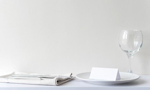 레스토랑에서 하얀 접시에 빈 초대 카드입니다. 테이블이 있는 레스토랑 내부, 축하하기 전 칼붙이, 흉내내기, 텍스트 공간