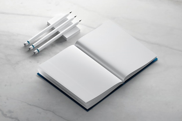 Blank journal book mockup with pencils on marble surface