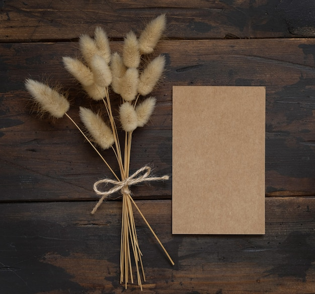 Blank kraft paper card on brown wooden table with dried flowers bouquet aside top view