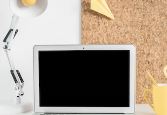 Blank laptop screen on desk with lamp and cork board