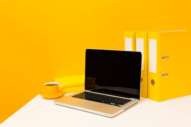 Blank laptop and yellow folders
