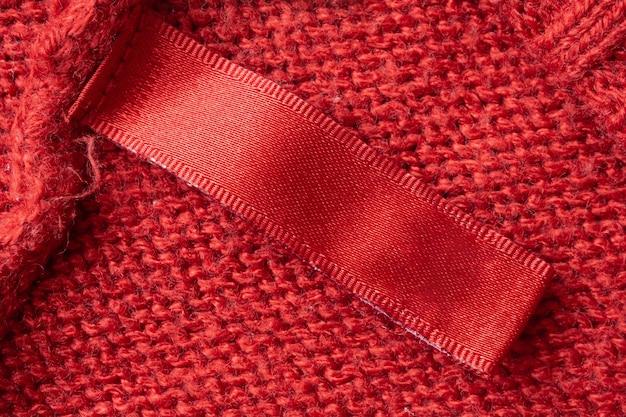 Пустая этикетка одежды для стирки на красном фоне текстуры трикотажной ткани