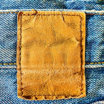 Blank leather label sewed on a blue jeans close-up