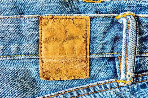 Blank leather label sewed on a blue jeans