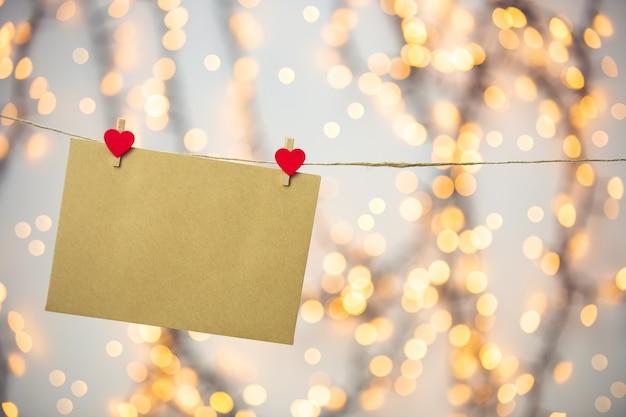 空白の手紙、赤いハートでぶら下がっている封筒やグリーティングカード、ロマンチックなラブレター、バレンタインデーのコンセプトボケ背景、コピースペースロマンチックなデザイン