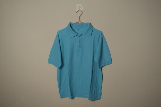 壁の背景正面側面図でハンガーに空白の水色のカジュアルなtシャツのモックアップ