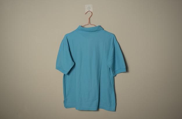 壁の背景の背面図でハンガーに空白の水色のカジュアルなtシャツのモックアップ