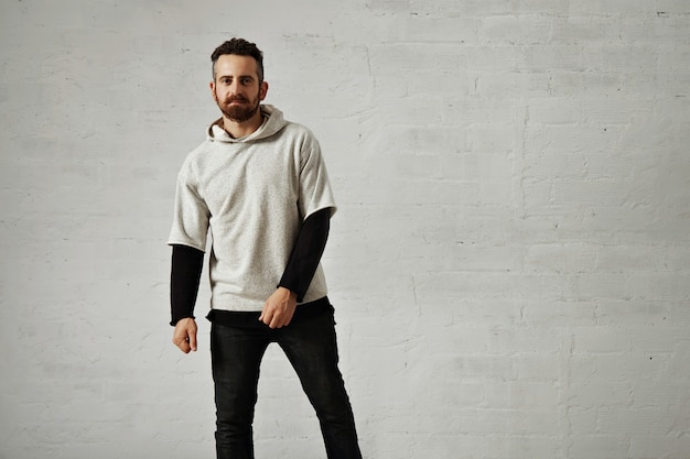 Blank light gray sweatshirt presented by a young hipster with a beard portrait with white walls