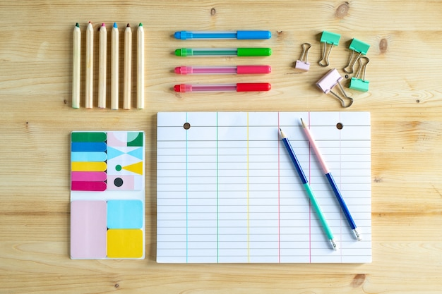 Blank lined page of notebook with two pencils and group of clips, sets of crayons and erasers near by