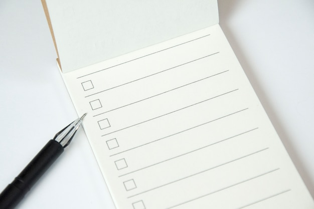 Blank to do list planner with checklist and black pen on white background, close up