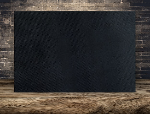 Blank long black fabric canvas frame at grunge brick wall and wood floor