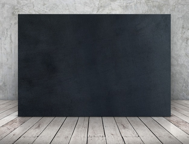 Blank long black fabric canvas frame leaning at concrete wall on wooden plank floor