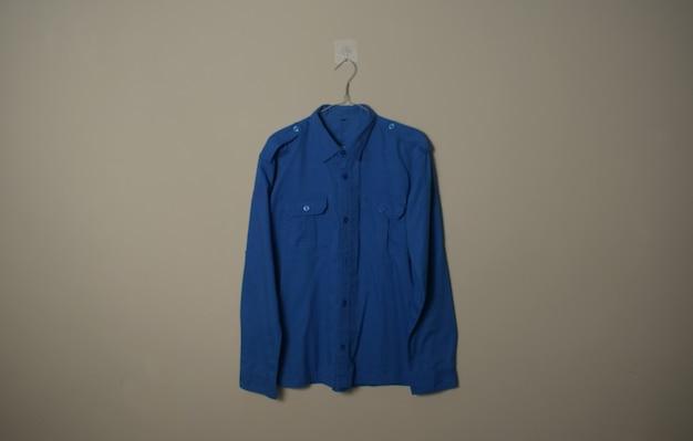 背景の壁の正面側面図のハンガーに空白の長袖青い屋外シャツのモックアップ