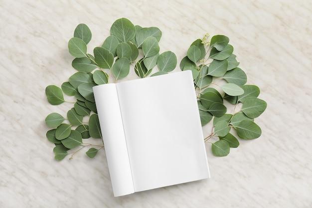 빈 잡지와 밝은 배경에 나뭇잎