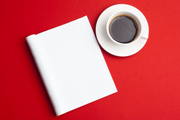 Blank magazine and cup of coffee on a red background