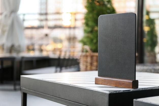 屋外のカフェのテーブルの上の空白のメニューボード