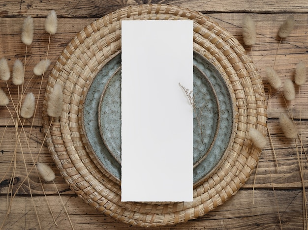 Пустая карточка меню на тарелке на деревянном столе с богемными украшениями и сушеными растениями, вид сверху. макет свадебной открытки в стиле бохо