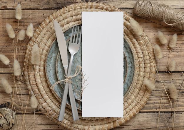 Пустая карточка меню на тарелке с вилкой и ножом на деревянном столе с богемными украшениями и сушеными растениями, вид сверху. макет свадебной открытки в стиле бохо