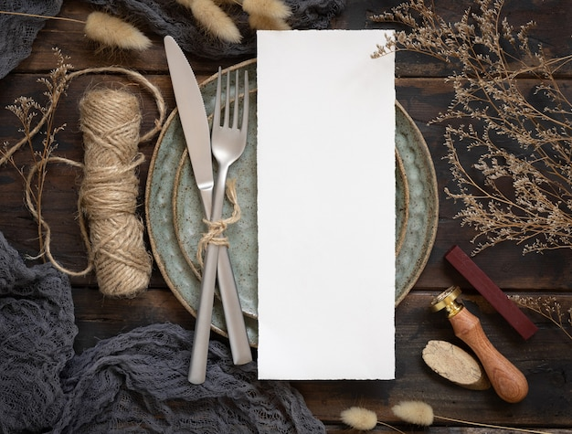 Blank menu card on plate with fork and knife on wooden table with bohemian decorations and dried plants, top view. boho wedding invitation card mockup