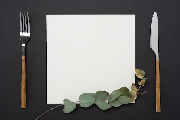 Blank menu or card with knife, fork, square paper decorated with gold eucalyptus branch on a black table.