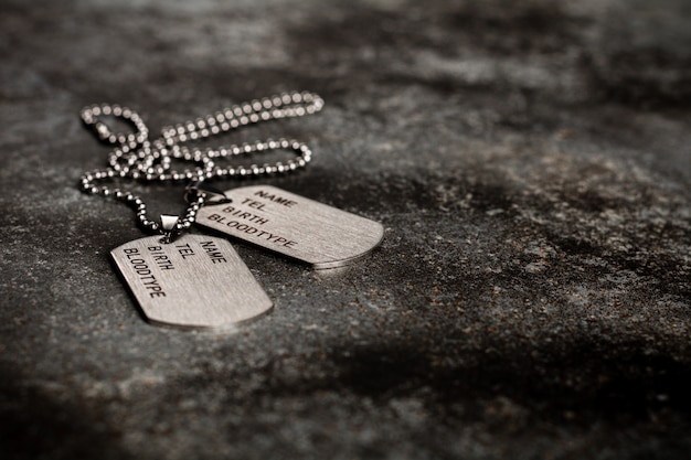 Blank military dog tags on abandoned rusty metal plate.  memories and sacrifices .