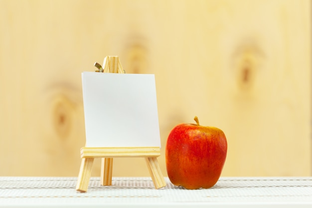 Blank mini canvas on easel on wooden table, copy space