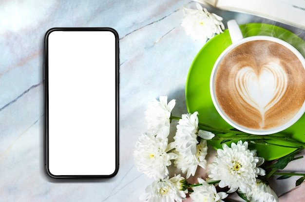 Blank of mobile phone on marble top table and coffee cup